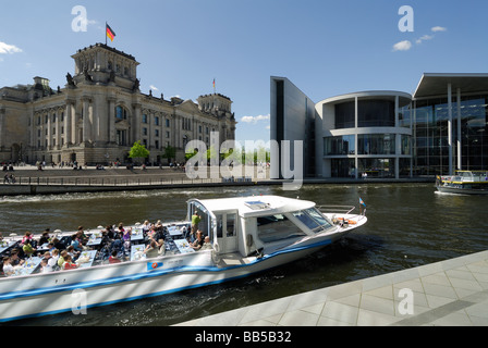 Berlin Germany Pleasure boat on the River Spree passes the Reichstag left and Paul Löbe Haus right - Stock Photo