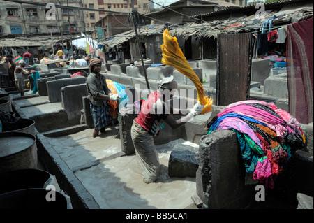 Dhobi flogging laundry in Dhobi Ghats, Mumbai, India - Stock Photo