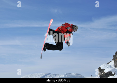snowboarder performing a jump stunt - Stock Photo