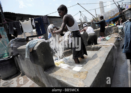 A Dhobi Waller hangs out laundry to dry at d - Stock Photo