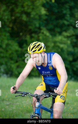 Mature male rider shows concentration as he ascends hill in the Basildon Off-Road Triathlon held in Essex England - Stock Photo