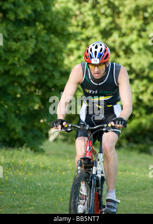 Male rider shows concentration as he ascends hill in the Basildon Off-Road Triathlon held in Essex England UK - Stock Photo