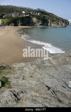 Village of Aberporth, Wales. Waves breaking on the west beach of Aberporth, with Pen Trwyn Cynwyl in the foreground. - Stock Photo