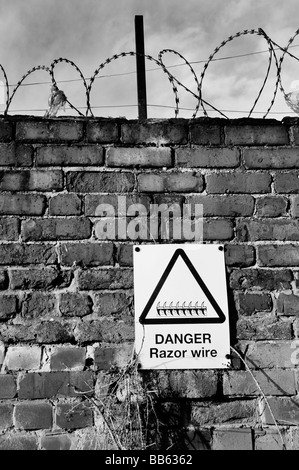A danger sign on a brick wall warning of razor wire - Stock Photo