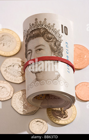 new and unused roll of UK Sterling mint ten pound bank notes rolled up lying on mint unused coins. - Stock Photo