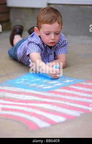 Young boy drawing American flag on sidewalk with chalk - Stock Photo