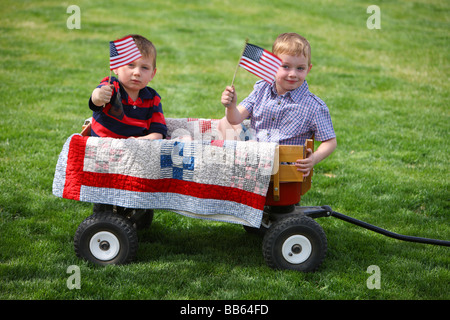 Two young boys sitting in wagon with American Flags - Stock Photo