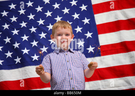 Young boy waving sparklers in front of American flag - Stock Photo