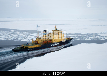 Russian Icebreaker expedition Cruise Ship moving through thick ice pack  in Antarctica people and helicopter on - Stock Photo