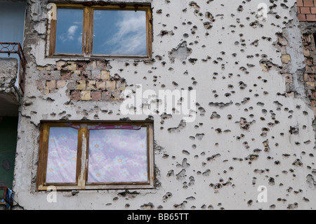 Facade of a house is riddled with bullet holes from the 1992-95 war in downtown Sarajevo, Bosnia Herzegovina - Stock Photo