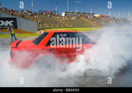 Drag racing HR31 Nissan Skyline performing a burnout prior to racing on a drag strip race track - Stock Photo