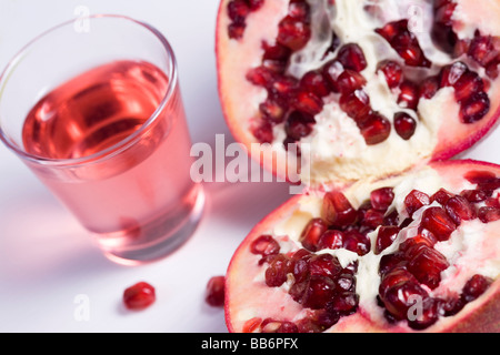 Pmegranate cut in half on white background and glass of juice - Stock Photo