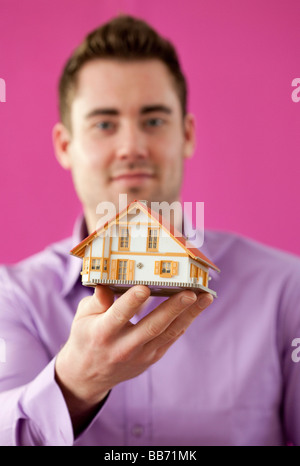 Young man holding a little house - Stock Photo