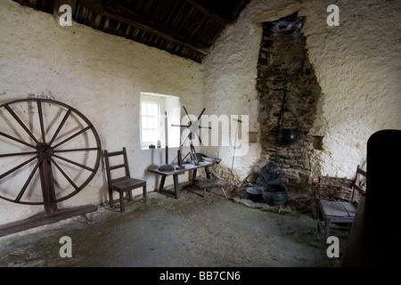 Eighteenth Century Irish Cottage Interior. The interior of a 18th century cottage with spinning wheel and open fireplace - Stock Photo