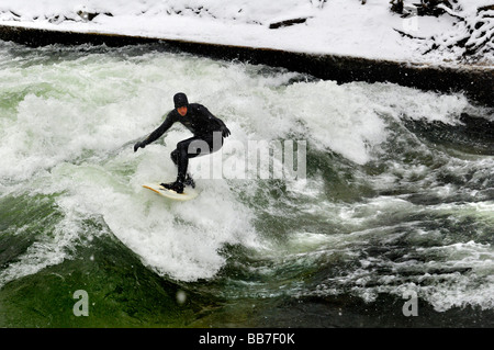 Surfer in Eisbach stream in winter, Munich, Bavaria, Germany, Europe - Stock Photo