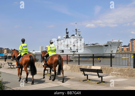 Royal Navy warship HMS Illustrious light aircraft carrier moored in River Thames Greenwich London passing mounted police patrol