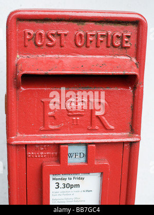 British Post Office Box. A red painted cast iron letter box in a wall with ER II and a crown. - Stock Photo