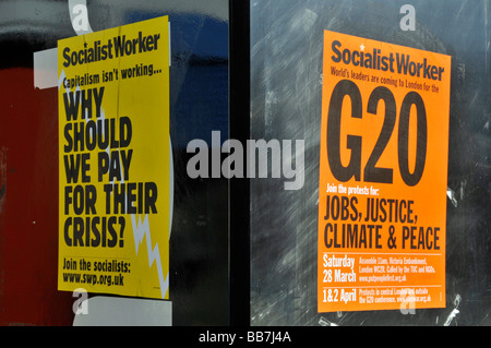 Socialist Worker posters stuck on side of phone box during the G20 summit in London - Stock Photo