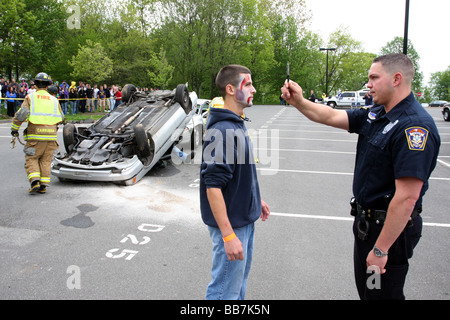 A police officer gives a teenager a DUI test during a mock Drunk driving accident at a USA High School - Stock Photo