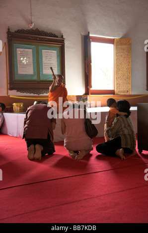 An elderly Buddhist monk giving his blessing to a Thai family in a temple in Chiang Mai Thailand - Stock Photo