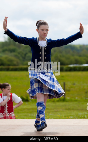 Female Highland Dancer dancing in a competition on an outdoor stage. - Stock Photo