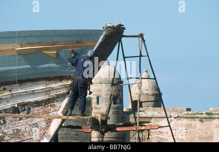 Carpenter standing on scaffolding at the dry dock repairing the bow of a fishing vessel with fortress towers behind, - Stock Photo