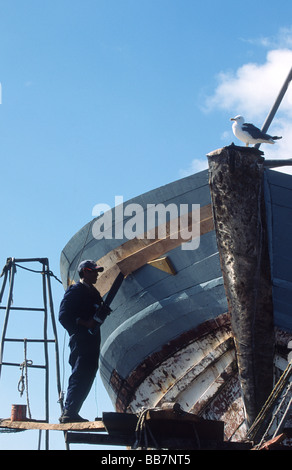 Carpenter standing on scaffolding at the dry dock repairing the bow of a fishing vessel, port of Essaouira, Morocco - Stock Photo