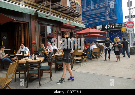 A woman texts at an outdoor cafe in the New York neighborhood of Chelsea on Saturday May 9 2009 Frances M Roberts - Stock Photo
