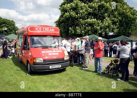 People queuing to buy ice cream from an ice cream van - Stock Photo