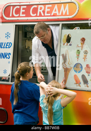 Two young children buying ice cream from an ice cream van - Stock Photo