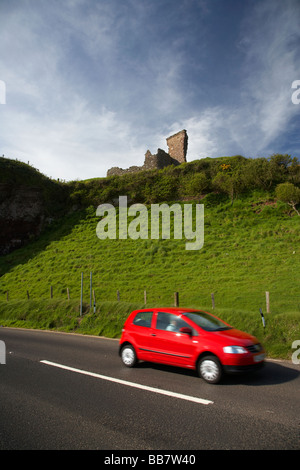 car touring the antrim coast beneath red bay castle on the A2 causeway coastal route coast road County Antrim - Stock Photo