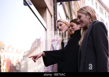 three women are looking in a shop window - Stock Photo