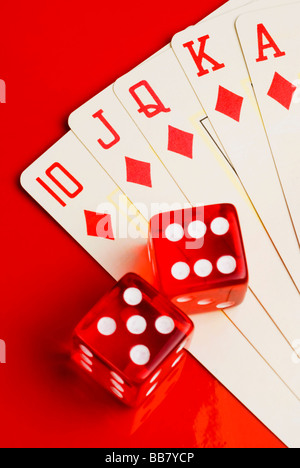 ace king queen jack ten of the same suit composing a Royal Flush in Poker game with two dices over a red surface - Stock Photo