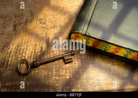 old key and  accounting book, on a rustic table, with light coming from a near window.Resembling the atmosphere - Stock Photo