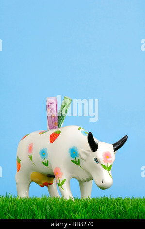 Ceramic cow with blossoms, piggy bank on grass - Stock Photo