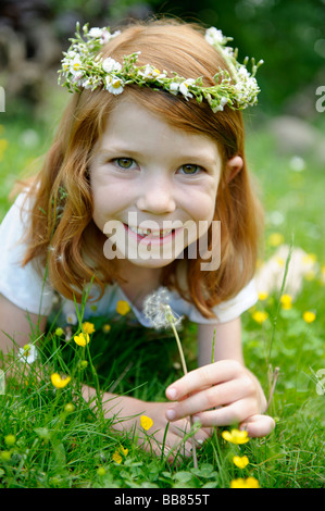 Young girl wearing a floral wreath in her hair holding a dandelion clock - Stock Photo