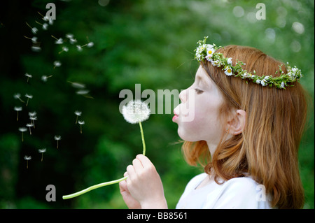 Young girl wearing a floral wreath in her hair blowing a dandelion clock - Stock Photo