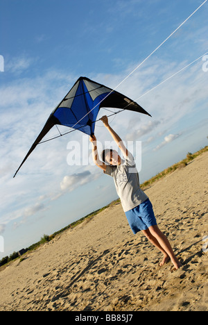 Boy flying kite, kite flying, kiting on the beach - Stock Photo