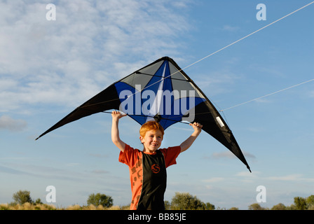 Boy flying kite, kite flying, kiting - Stock Photo