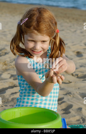 Girl playing on the beach with a hermit crab, seaside of the Adria, Venetia, Venice, Italy, Europe - Stock Photo
