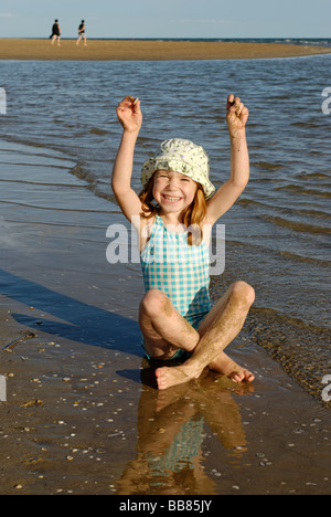 Girl with sunhat on the beach, waterfront, seaside of the Adria, Bibione, Venetia, Venice, Italy, Europe - Stock Photo