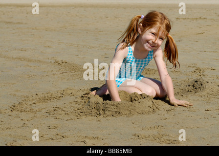Girl lying and playing on the beach, seaside of the Adria, Bibione, Venetia, Venice, Italy, Europe - Stock Photo