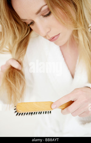 Portrait of young woman in dressing gown brushing her hair - Stock Photo