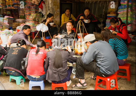 mobile food shop in hanoi street hawker selling noodle have a few plastic chairs for sit and eat then move to somewhere - Stock Photo