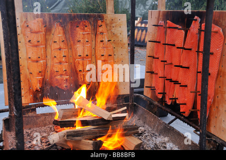 Salmon being smoked over open fire, Finnish Christmas market in Stuttgart, Baden-Wuerttemberg, Germany - Stock Photo