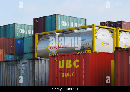 Container depot, stacked standard ISO containers and tank containers - Stock Photo