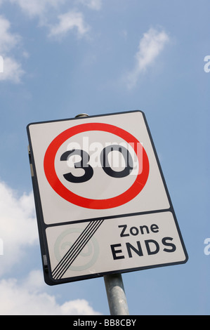 Road sign showing that traffic is leaving a 20 mph zone and the speed limit is now 30 mph in a town in England - Stock Photo