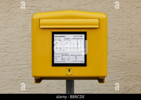 Yellow mail box of the German post office in front of a roughcast wall - Stock Photo