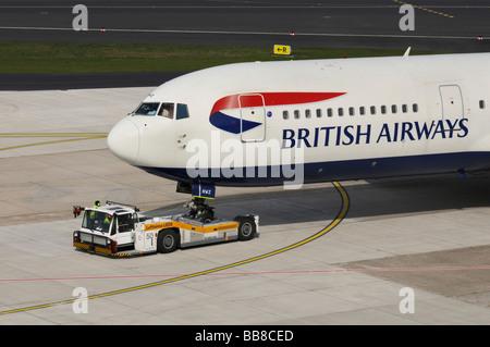 Marshalling yard vehicle with airplane of the British Airways on the runway, Duesseldorf International Airport, - Stock Photo