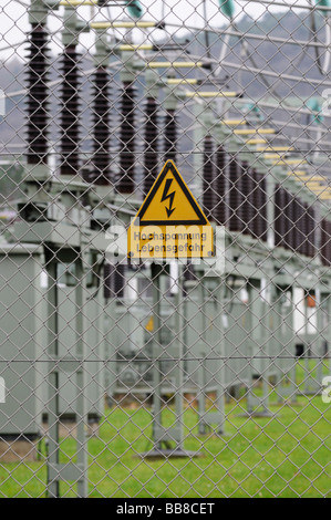 Sign, high voltage, risk of fatal injury, on a wire mesh fence, in front of an electrical transformer station - Stock Photo
